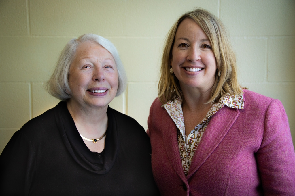 Two women are standing next to each other and smiling broadly. On the left a white woman has silver hair and a black top and on the right a white woman had shoulder length blonde hair and is wearing a bright pink jacket with a patterned shirt beneath it.